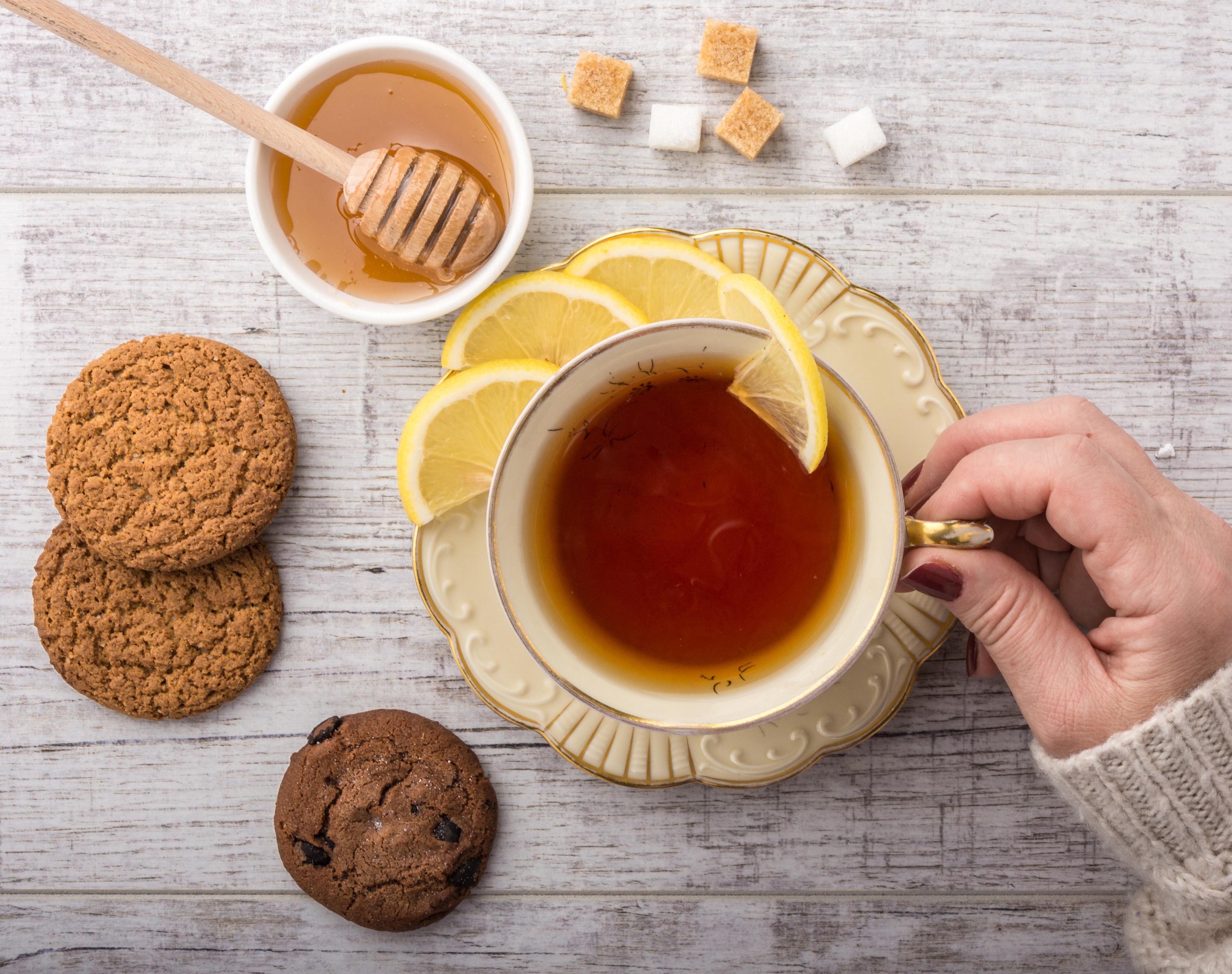 Tasse avec du thé des montagnes, miel, citron et cookies
