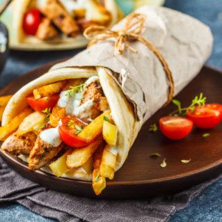 Souvlaki aux brochettes de poulet, pain pita, frites, tzatziki et tomates