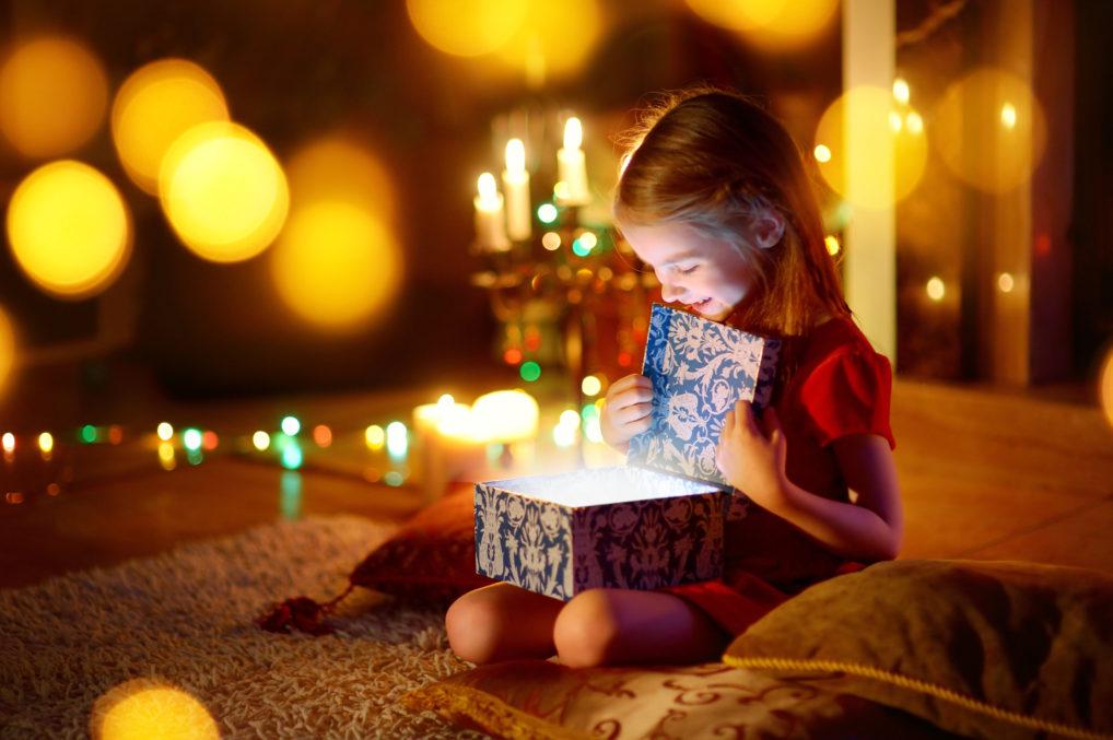 Une fille qui ouvre son cadeau de Noël ou Nouvel An
