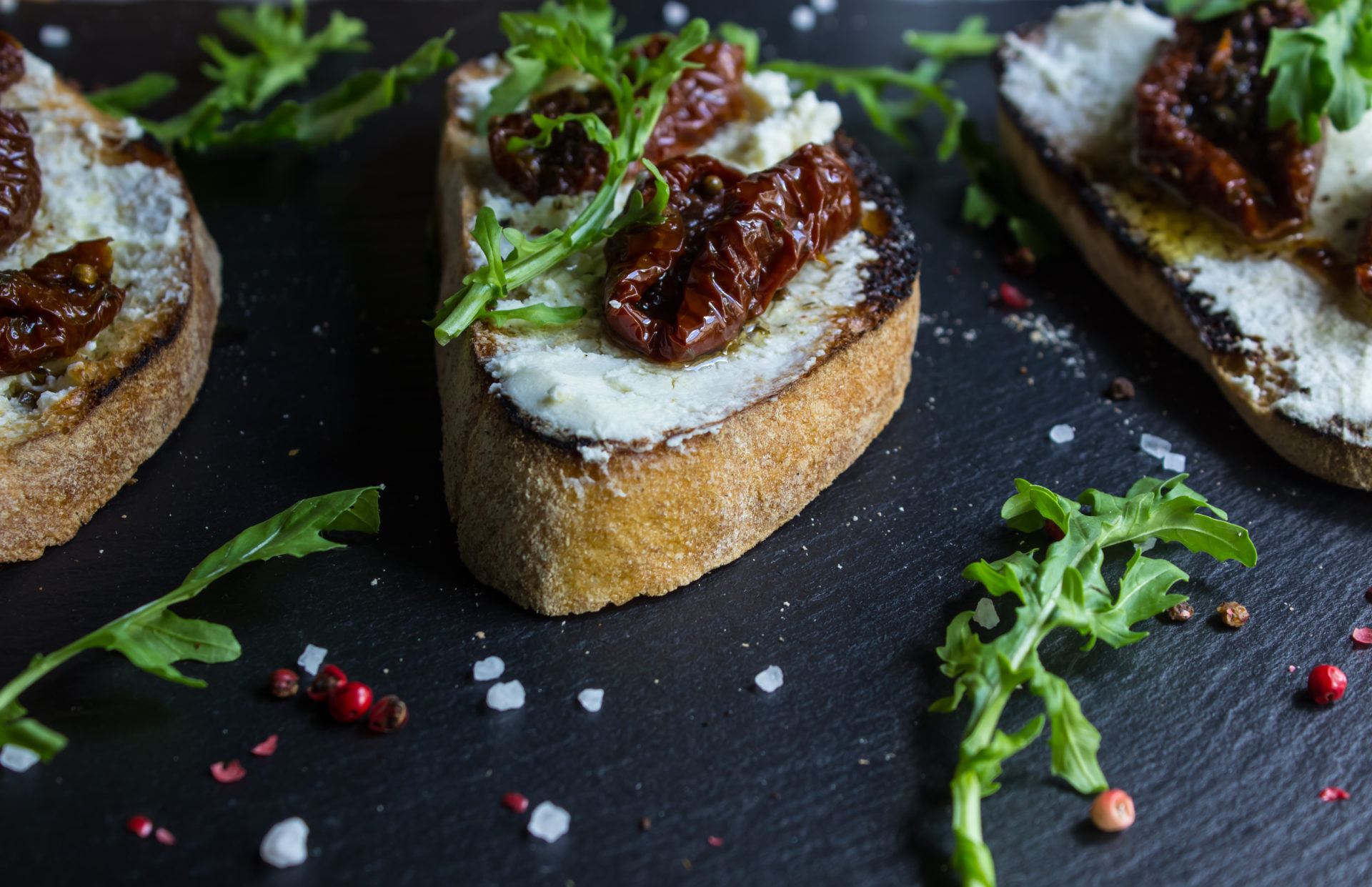 Bruschetta with fresh cheese, sun-dried tomatoes and thyme
