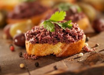 Tapenade aux olives grecques de kalamata sur une tranche de pain pour l'apéritif